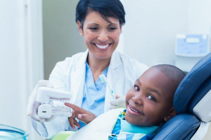 Dentist showing boy how to brush manassas va family dentist