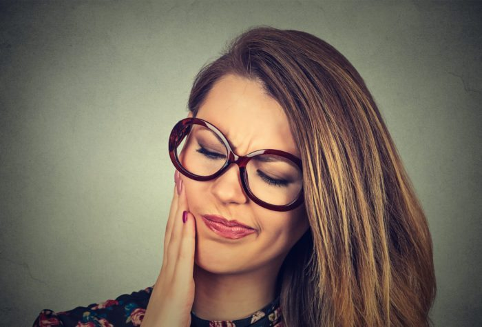 woman in glasses with sensitive toothache pain manassas smile va dental emergeny