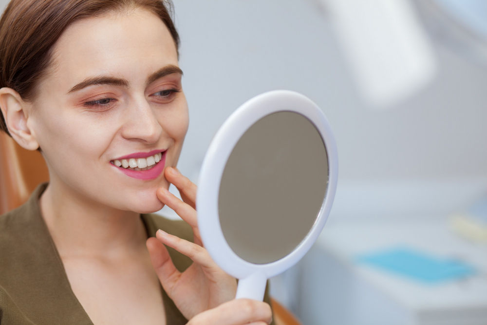 best dentist in Manassas MA | Woman smiling at mirror.